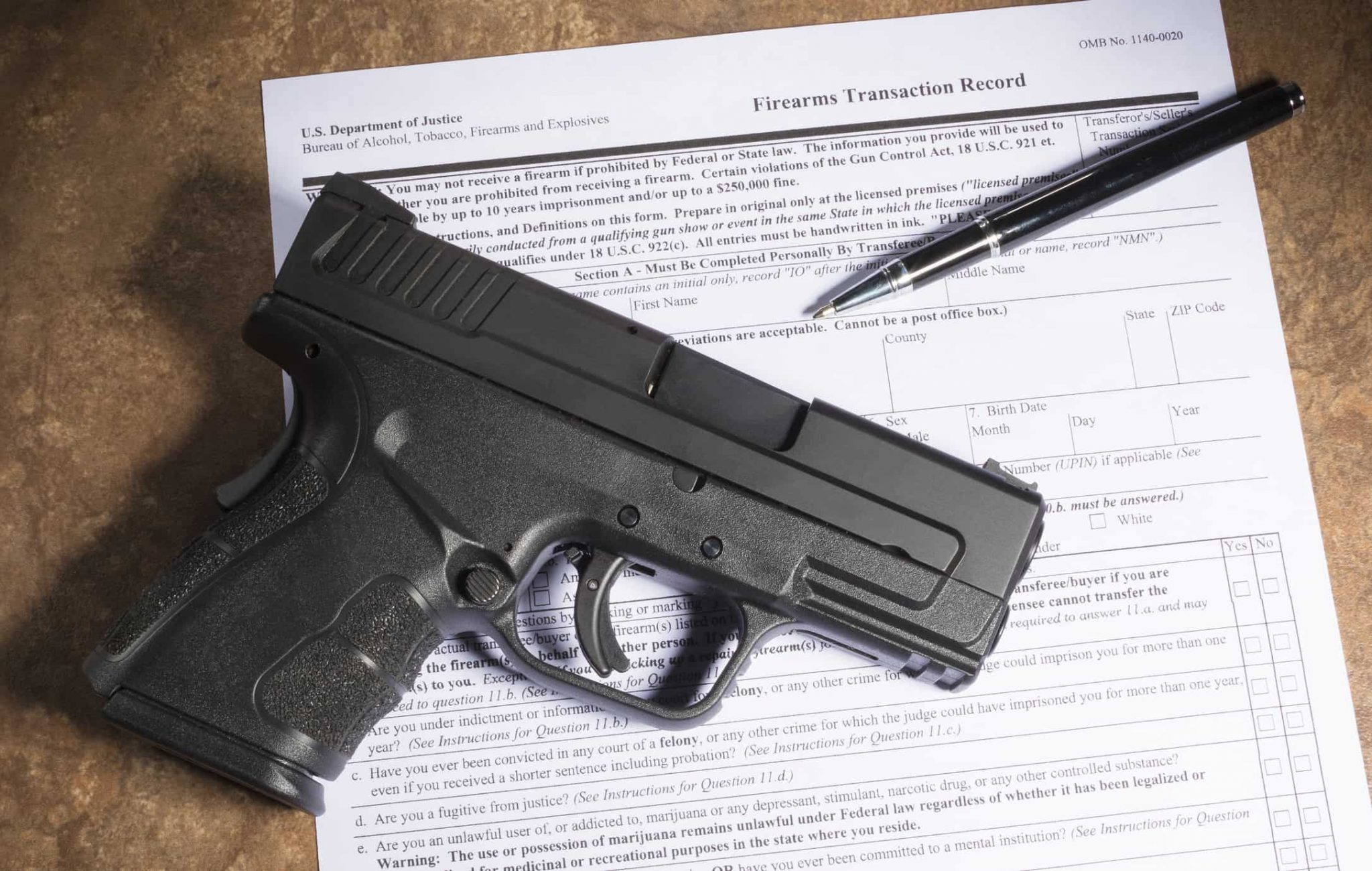 Polymer handgun and paperwork to purchase it on a beige counter