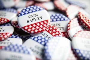 """Red, white, and blue buttons that read: """"gun safety"""""""